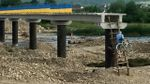 Люди по драбині з велосипедами на спині вилазять на недобудований міст