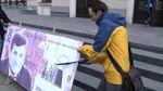 В Запорожье активисты распилили бутафорскую банкноту с фотографией городского головы