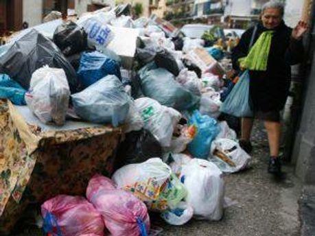 Женщина обходит гору мусора