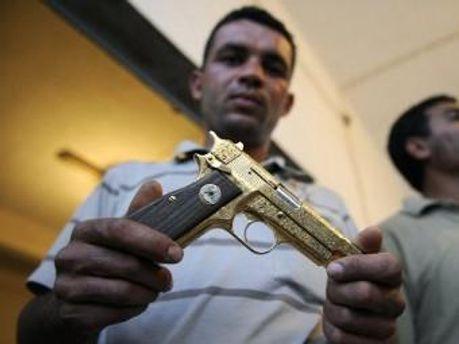 Боец НПР демонстрирует золотой пистолет Каддафи