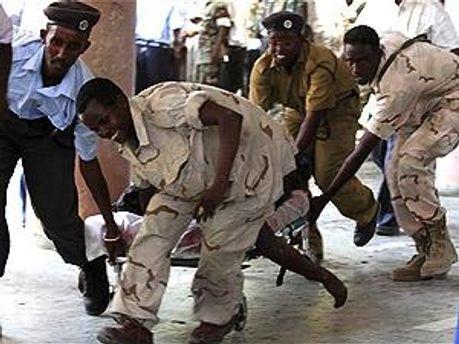 Сомалийские солдаты выносят раненого из здания театра