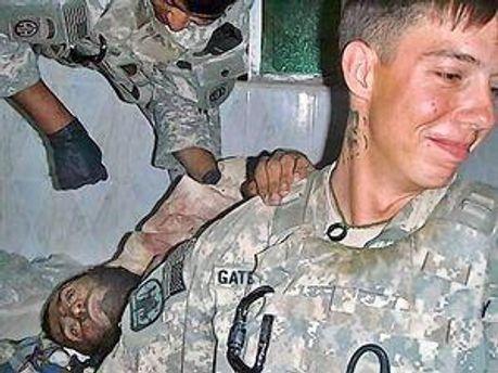 Американский солдат позирует возле погибшего