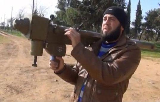 Сирийский повстанец учится управлять оружием, полученным из неизвестных источников