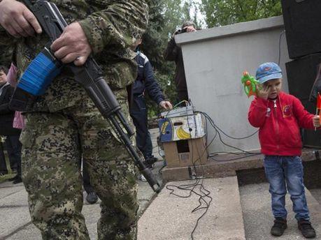 Вооруженный боевик рядом с ребенком