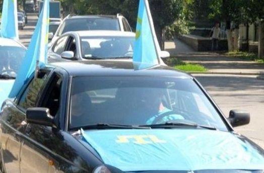Автомобіль з кримськотатарськими прапорами