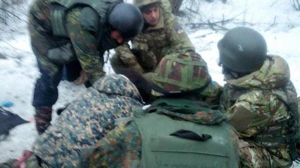 Украинские военные вокруг раненого товарища