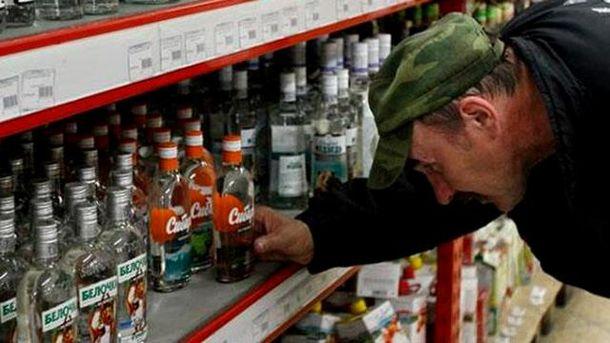 Мужчина выбирает алкогольный напиток в супермаркете