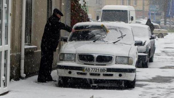 Чоловік чистить машину від снігу