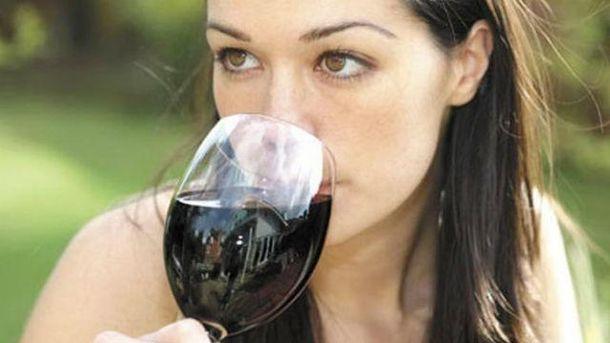 Наслаждается красным вином