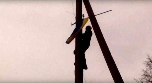 Український воїн встановлює прапор України на окупованій території