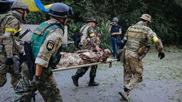 Бойцы АТО несут раненого