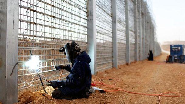 Мужчина сваривает забор