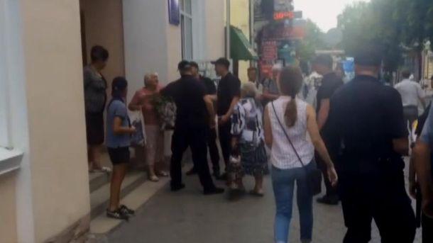 Поліцейські забирають пенсіонерку до відділку