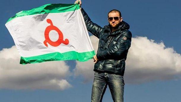 Чоловік тримає у руках прапор Інгушетії