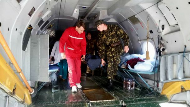 Виносять  військового пораненого з літака