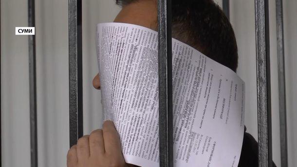 Підозрюваний Олександр Самковий ховає своє обличчя від журналістів
